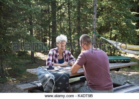 Paio di carte da gioco al campeggio tavolo da picnic nei boschi Foto Stock