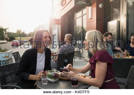 Donna sorridente gli amici a bere vino a sidewalk cafe Foto Stock