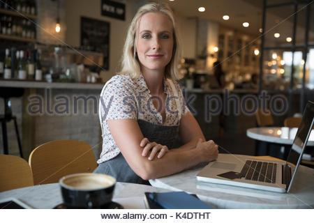 Ritratto femminile fiducioso cafe proprietario lavora al computer portatile Foto Stock