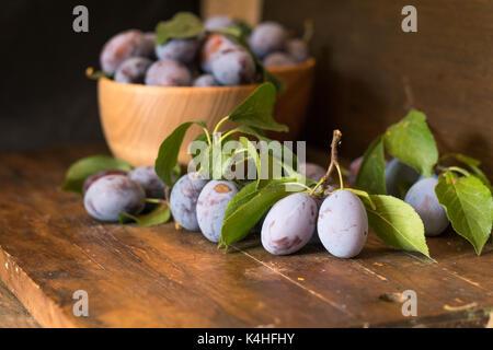 Prugne fresche con foglie verdi in vaso di legno sul legno scuro. tabella profondità di campo. tonica. Foto Stock