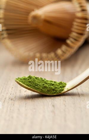 Bambù giapponese matcha cucchiaio, chashaku, con tè verde e chasen sullo sfondo Foto Stock
