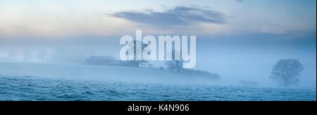 Un paesaggio ghiacciato all'alba con una vecchia casa colonica e palazzi inizio per essere avvolta in una fitta nebbia di congelamento di arrotolamento dalla valle al di sotto vicino Foto Stock
