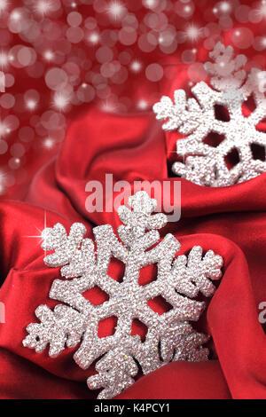 Il simbolo del fiocco di neve sul raso rosso sfondo Foto Stock