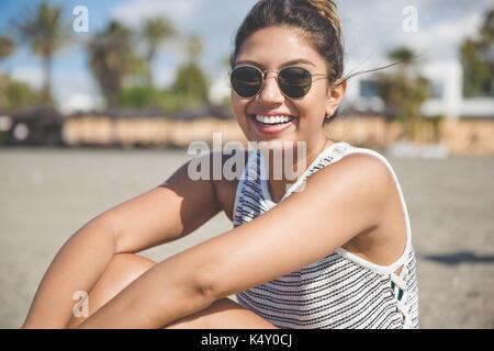 Ritratto di giovane e bella donna seduta sulla spiaggia di ridere Foto Stock
