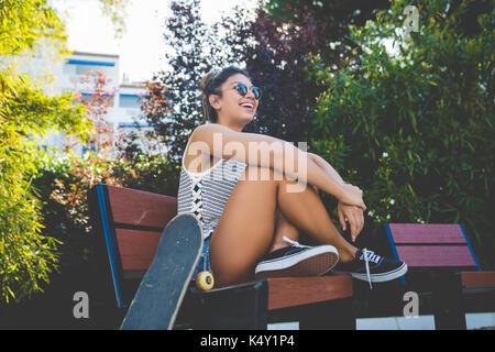 Ritratto di giovane donna graziosa seduto sulla spiaggia con lo skateboard ridere Foto Stock