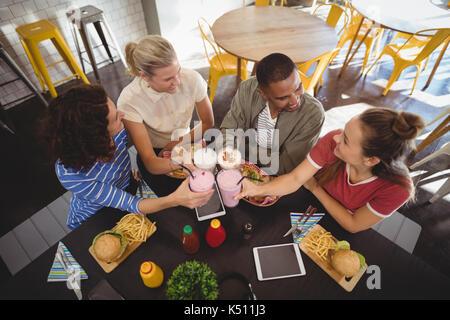 Alta vista angolare di sorridere giovani amici sollevamento toast mentre è seduto a tavola in un coffee shop Foto Stock