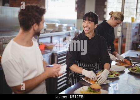 Allegro cameriere e femmina di lavoro dello chef in cucina presso il cafe Foto Stock