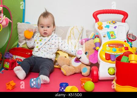 Nove mesi baby ragazza seduta sul pavimento e giocare con i suoi giocattoli Foto Stock