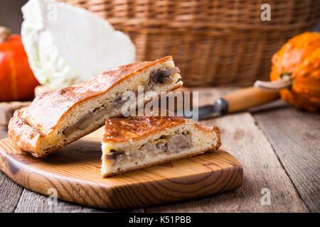 Fette di cavolo e funghi con torta di formaggio sulla tavola in legno rustico, comfort sano cibo vegetariano Foto Stock