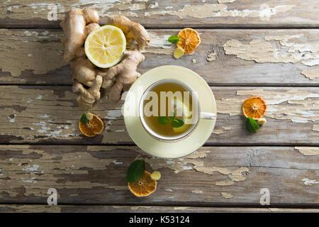 Vista aerea di limone e foglie di menta in tè allo zenzero su weathered tavolo in legno Foto Stock