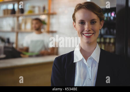Ritratto di felice proprietario femmina con cameriere lavora in background al cafe Foto Stock
