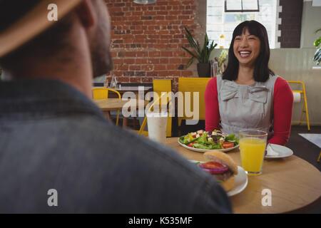Felice giovane donna guardando l uomo mentre è seduto in cafe Foto Stock