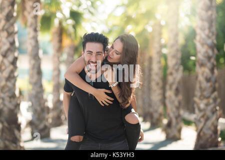 Ritratto di giovane uomo felice di dare la sua ragazza un piggyback ride Foto Stock