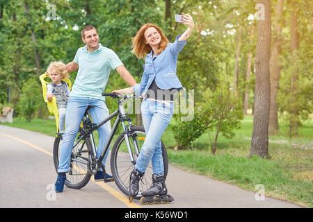 La famiglia felice in Bicicletta Equitazione presso il parco Foto Stock