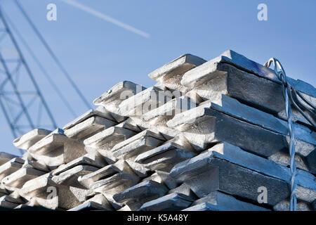 Shiny lingotti di alluminio con una gru in background mentre un piano è volare sopra Foto Stock