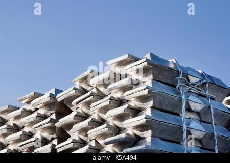 Shiny lingotti di alluminio ed un cielo blu Foto Stock
