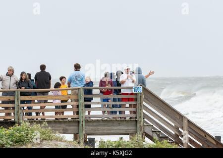 La gente guarda i surfisti in Extreme Waves causato da una marea di serge uragano irma presso la follia di dilavamento Foto Stock