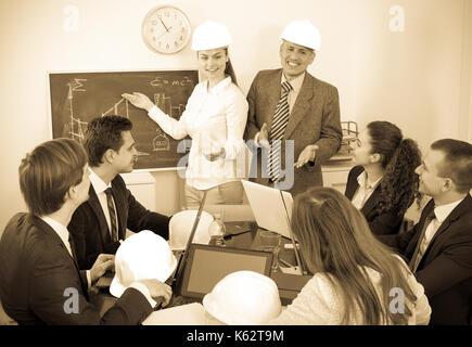 Professionisti sorridente con notebook e caschi con la presentazione del nuovo progetto in ufficio Foto Stock