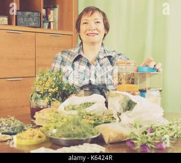Sorridente donna invecchiato con erbe a tavola in casa Foto Stock