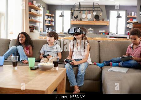 I bambini giocano gioco sul computer utilizzando la realtà virtuale auricolare Foto Stock