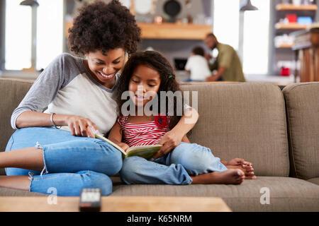 Madre e figlia seduti sul divano in sala lettura libro insieme Foto Stock