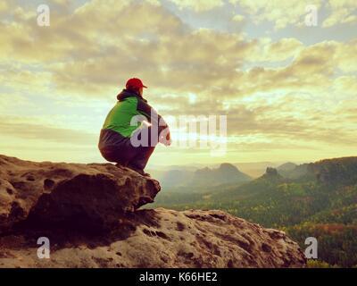 Da soli tourist prendere un periodo di riposo. escursionista in verde giacca  nera seduta sul 569b3fcde198