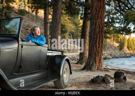 Donna seduta nel rinnovato carrello guardando il tramonto sul Lago Payette, McCall, Idaho, Stati Uniti d'America