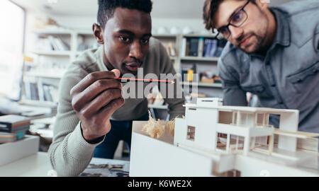 Due architetti maschi in ufficio a discutere il progetto di costruzione. Giovani uomini che lavorano insieme su Foto Stock