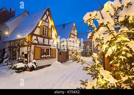 Un vecchio villaggio di strada con semi-case con travi di legno e le luci di Natale di notte durante la nevicata Foto Stock
