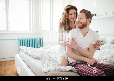 Bella coppia felice risveglio sorridente in camera da letto Foto Stock