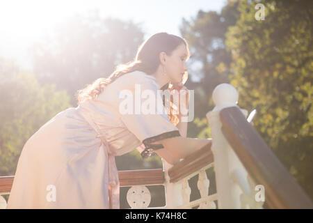 Vista laterale della sposa usando il cellulare mentre appoggiata sulla ringhiera di balcone Foto Stock