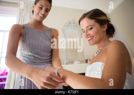 Sorridente damigella assistere sposa di vestirsi in sala di montaggio Foto Stock
