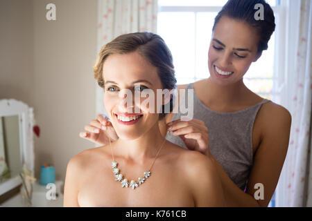 Damigella bride di fissaggio collana in spogliatoio Foto Stock