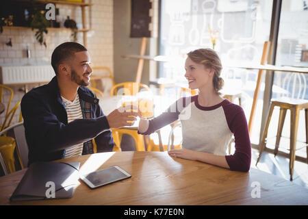 Sorridente giovani amici sollevamento toast con succo mentre è seduto a tavola in un coffee shop Foto Stock