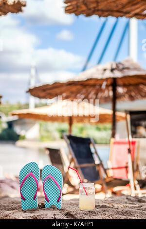 Pantofole con un drink sulla sabbia, vista d'acqua, spiaggia, estate, relax e divertimento Foto Stock