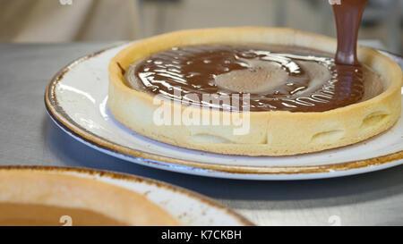 Colata di cioccolato sul pezzo di deliziose torte appena sfornate Foto Stock