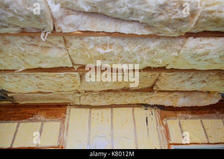Isolamento in fibra di vetro installati nel soffitto inclinato di un nuovo telaio house. isolamento per la casa Foto Stock