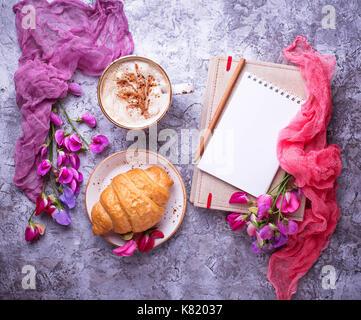 Caffè e Croissant, fiore e notebook. Foto Stock