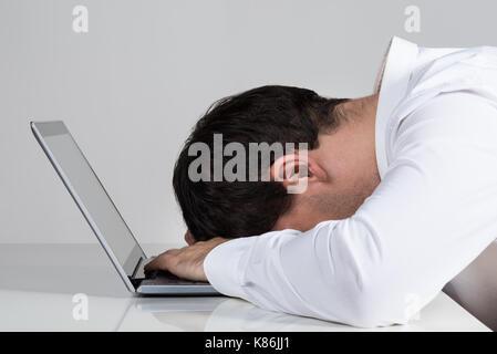 Vista laterale del sottolineato imprenditore appoggiata su laptop al banco contro uno sfondo bianco Foto Stock