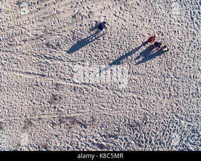 Ragazzi che giocano a sabbia in spiaggia con le ombre Foto Stock