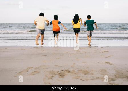 Bambini running presso la spiaggia insieme.amicizia concetto.Concetto di famiglia.il concetto di vacanza Foto Stock