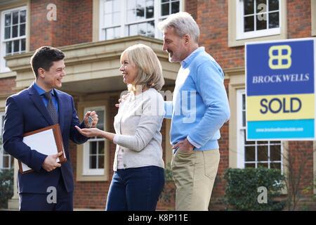 Coppia matura la raccolta chiavi per nuova casa da agente immobiliare Foto Stock