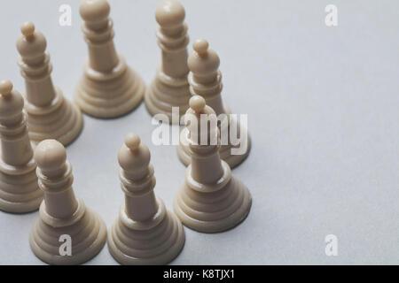 Partita scacchi a personaggi viventi pezzi su uno sfondo grigio. il concetto di strategia Foto Stock