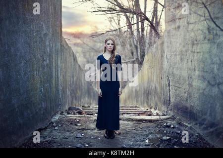 Bella ragazza solitaria in abiti lunghi nei pressi di cupo tunnel sul tramonto Foto Stock