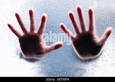Sagome di due mani di destra dietro il vetro bagnato Foto Stock