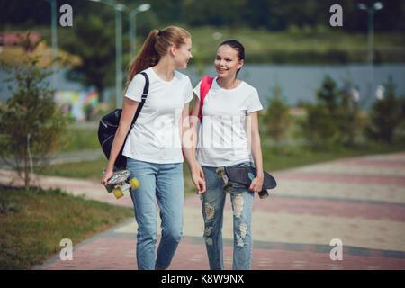 Le ragazze in bianco t-shirts sono a piedi lungo la strada e il trasporto di skateboard. mock up. Foto Stock