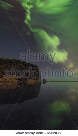 Green aurora, le luci del nord, formando una corona nel cielo e riflettendo su una laguna nel sud dell'Islanda. Foto Stock