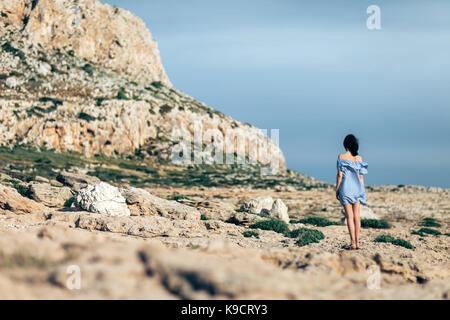 Vista posteriore della donna solitarie passeggiate sul deserto roccioso con drammatica sky Foto Stock