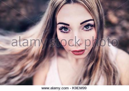 Modello russo fissando la telecamera. occhi blu-verde, biondo dei capelli ondulati, labbra rosse Foto Stock
