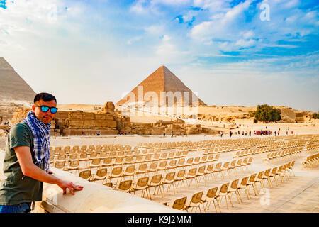 Guardando le sedie vicino la piramide del Cairo in Egitto Foto Stock